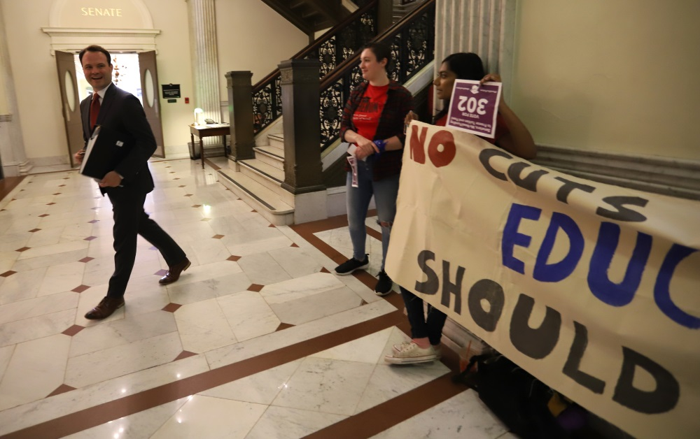 Sen. Eric Lesser walked past student protesters wi