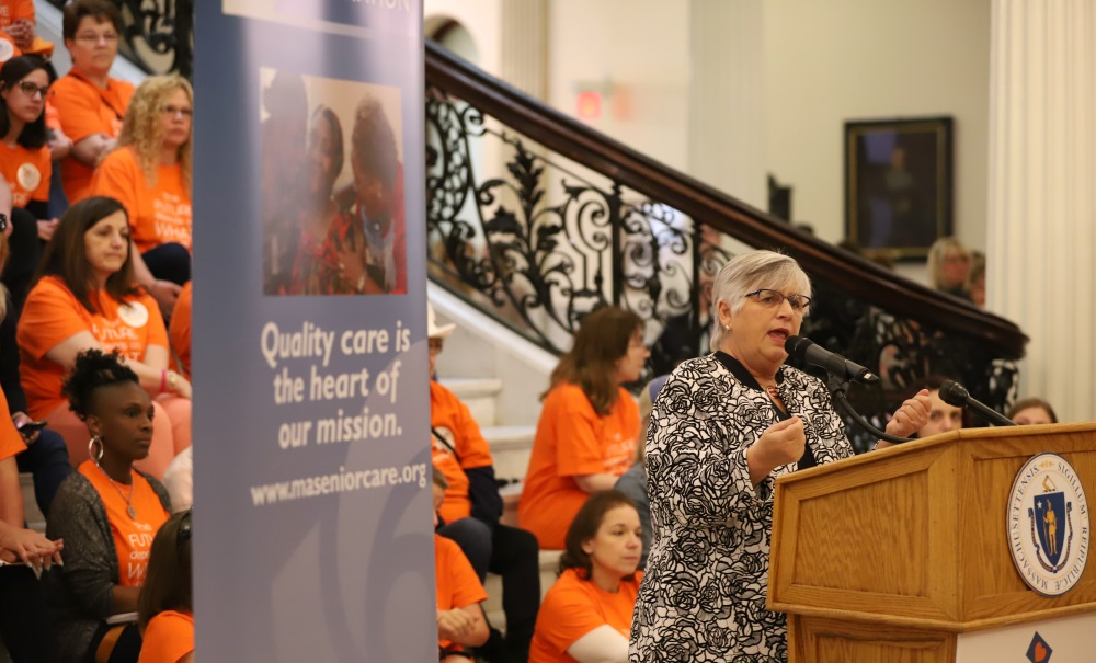 In front of a backdrop of nursing home advocates,