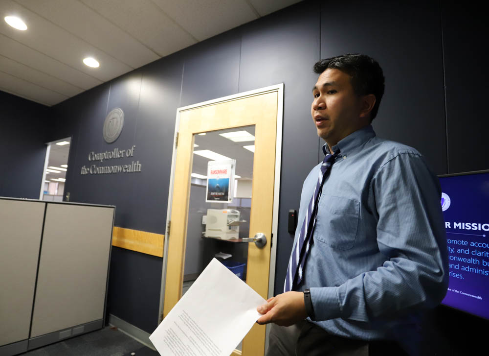 With two minutes until a 3 p.m. deadline when Comptroller Andrew Maylor was going to rake the fiscal 2019 surplus into the rainy day fund, his spokesman Michael Sangalang emerged from the office suite to say the $1 billion transfer was being postponed. [Photo: Sam Doran/SHNS]