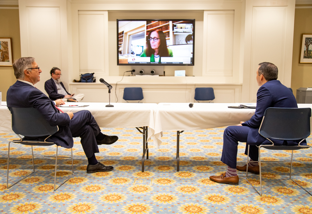"Sen. Michael Rodrigues (left), Rep. Aaron Michlewitz (right), and Treasurer Deborah Goldberg (on screen) waited while staff tried to fix a failed livestream of the ""virtual roundtable"" about COVID-19's impact on state revenues. [Photo: Sam Doran/SHNS]"