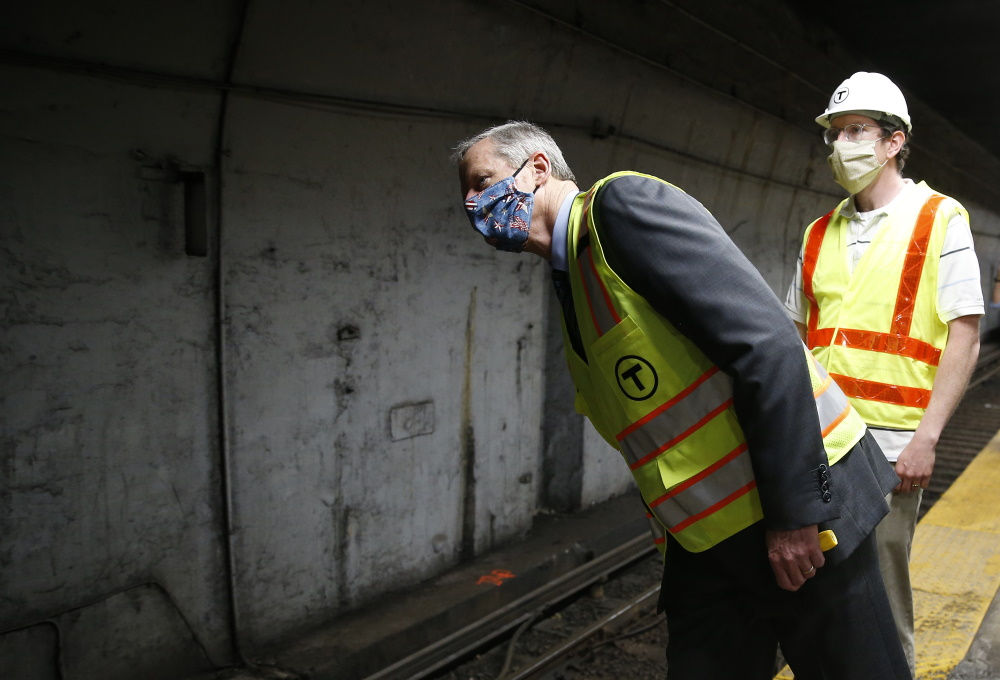 Gov. Charlie Baker peered down the tracks Wednesday at the Maverick Square Blue Line station. [Photo: Jessica Rinaldi/Boston Globe/Pool]