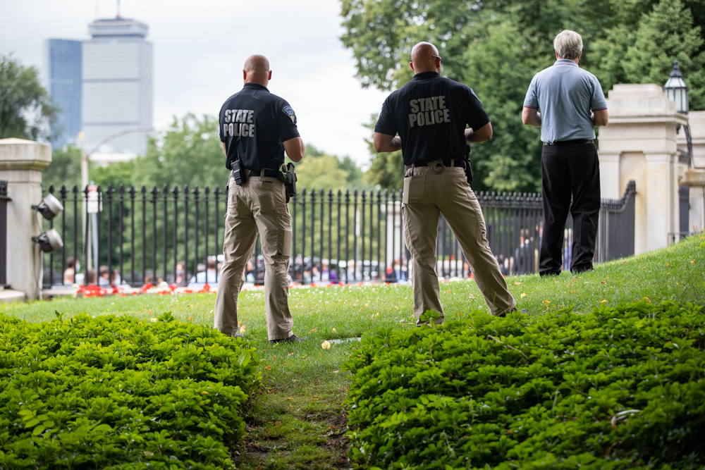 State Police troopers stood on the State House front lawn Monday while lawmakers on the sidewalk below unveiled the Senate's sweeping package of police reforms. [Sam Doran/SHNS]