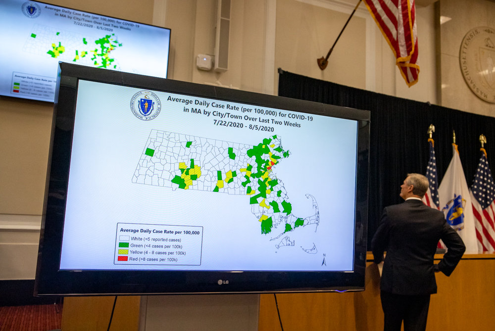 Gov. Charlie Baker looked up at a television screen displaying the new color-coded COVID-19 infection rate map during a Tuesday news conference. [Sam Doran/SHNS]