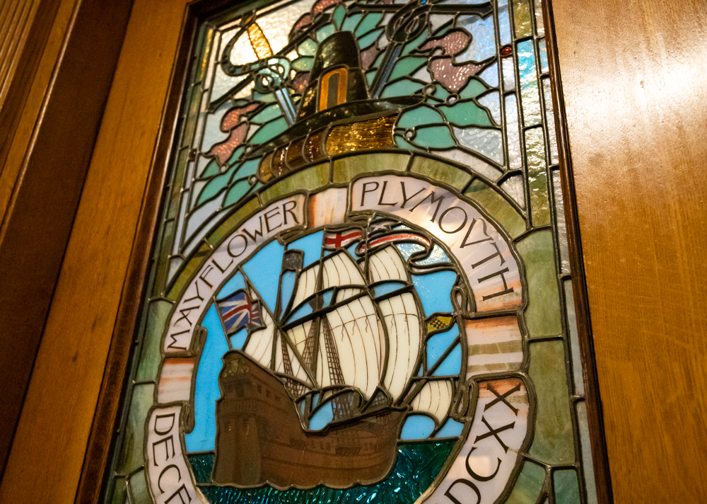 The Mayflower's 1620 voyage to Plymouth Colony is memorialized, surmounted by a Pilgrim's captain hat, in a stained glass window in a door to the Senate president's office at the State House. [Sam Doran/SHNS]