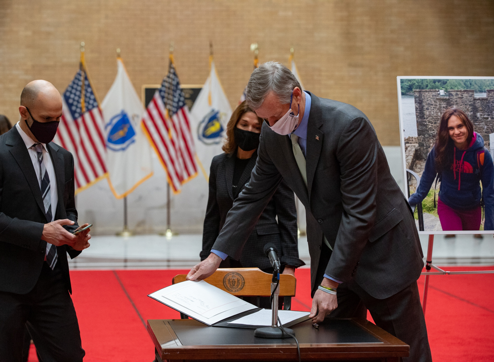 """One bill that met with Gov. Charlie Baker's approval was """"Laura's Law,"""" which aims to improve access to hospital emergency rooms and was named for the late Laura Levis (pictured at right). Levis' husband Peter DeMarco (left) joined Baker at a bill-signing ceremony Friday afternoon. [Sam Doran/SHNS]"""