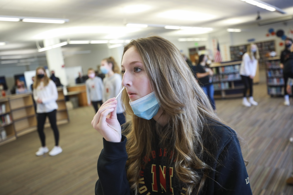 Student Emma Low self-administers a swab on Feb. 26 as part of a pooled COVID-19 testing program at Nock-Molin Middle School in Newburyport. [Nicolaus Czarnecki/Boston Herald/Pool]