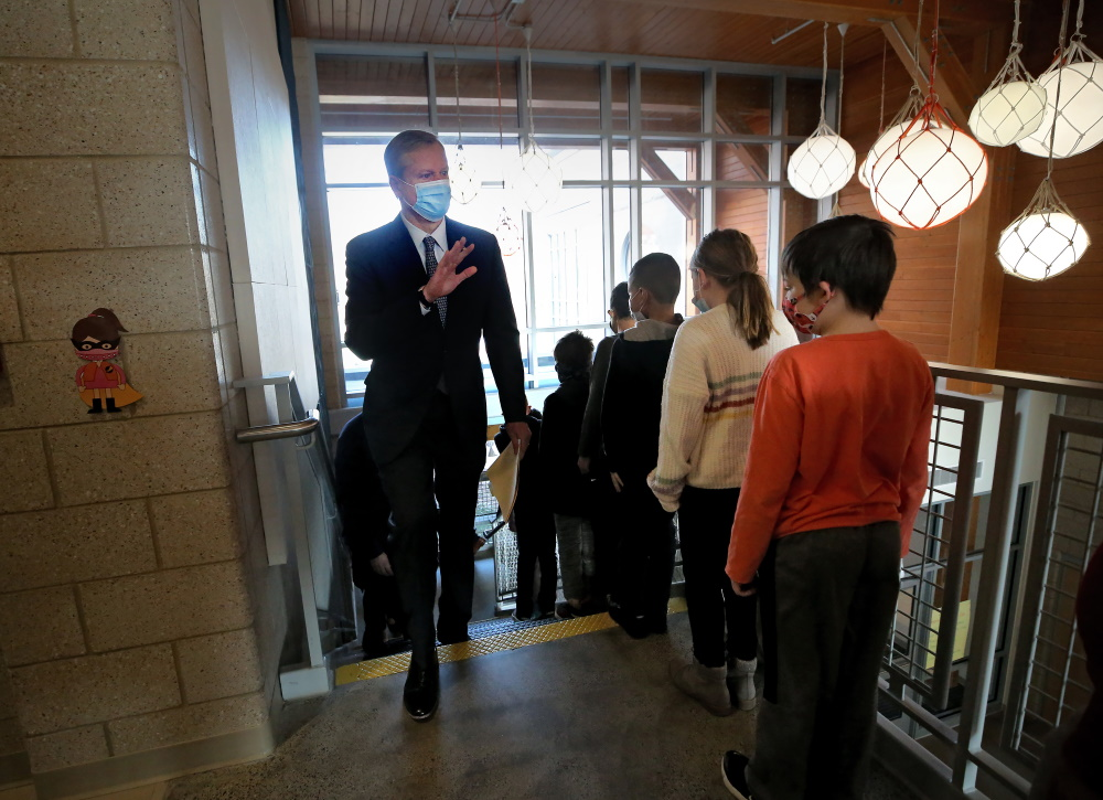 Gov. Charlie Baker waves to a line of students Wednesday during a visit to Gloucester's West Parish School, where pupils have been learning in person for more than 100 days. [Nancy Lane/Boston Herald/Pool]