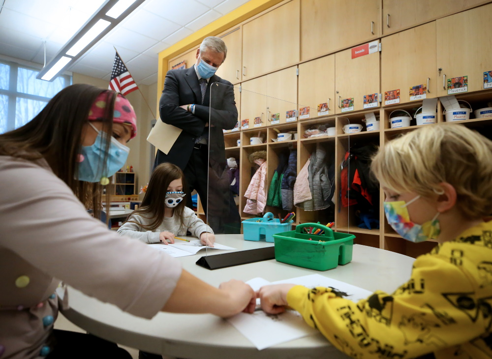 Gov. Charlie Baker watches a kindergarten teacher work with students on Wednesday as he visits West Parish School in Gloucester, where they have been holding in-person learning for 101 days. [Nancy Lane/Boston Herald/Pool]