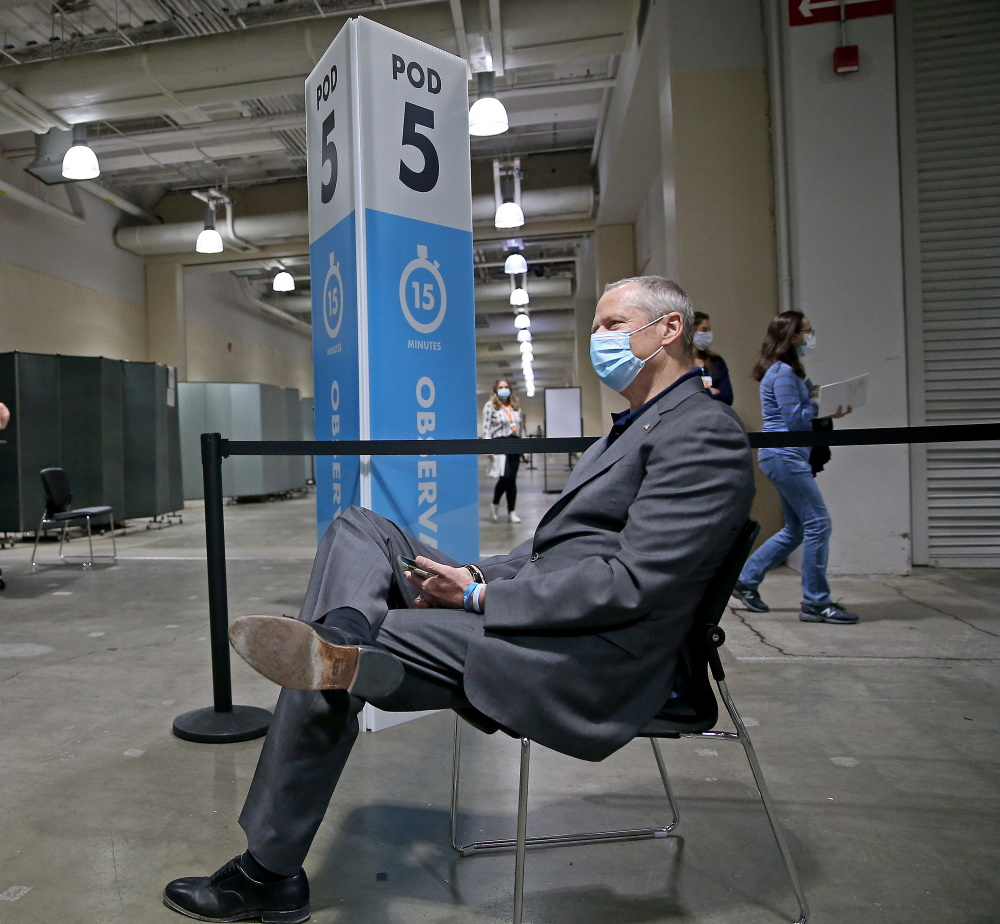 He's gotta wait 15 minutes, just like everybody else . . .  Gov. Charlie Baker waits in the observation area after receiving his first dose of Pfizer's COVID-19 vaccine at the Hynes Convention Center on Tuesday. [Matt Stone/Boston Herald/Pool]