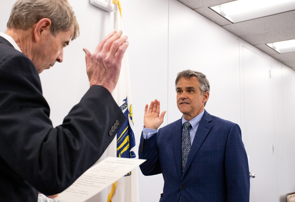 William Campbell, new director of the Office of Campaign and Political Finance, swears his oath of office Monday afternoon in a McCormack Building conference room with Secretary William Galvin presiding. [Sam Doran/SHNS]