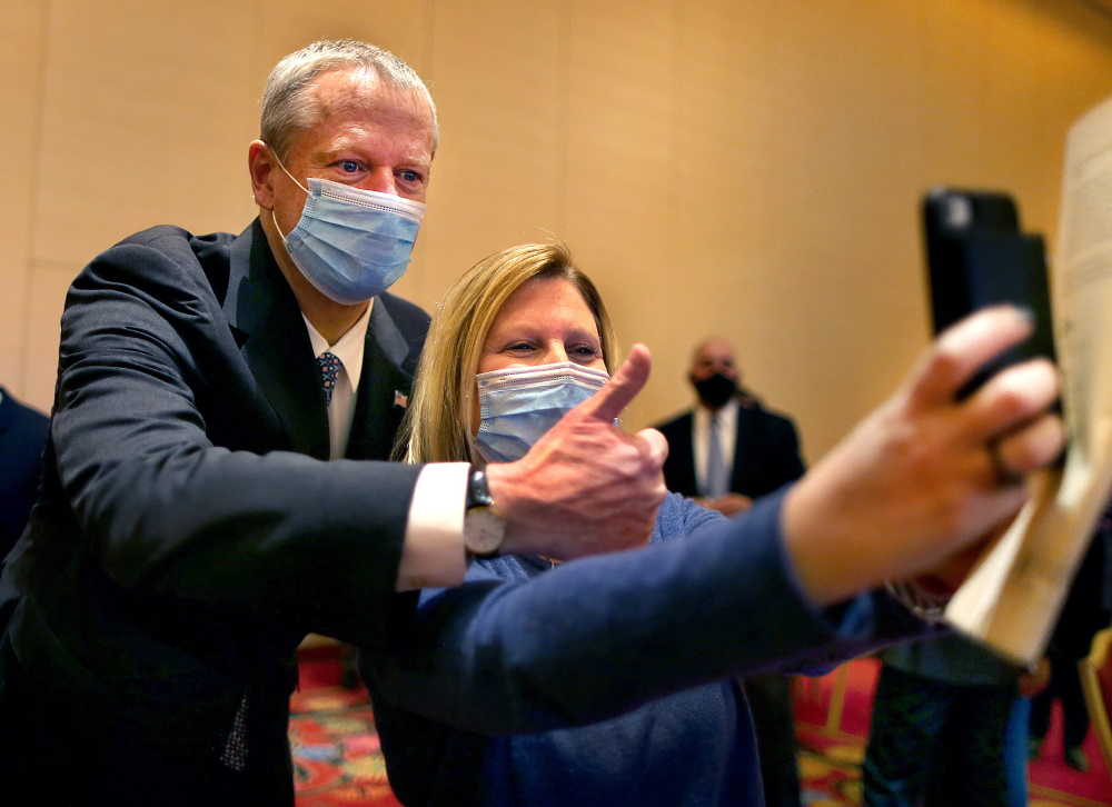 Gov. Charlie Baker gives a thumbs-up on Wednesday as Beth Franklin takes a selfie while waiting after getting her first Pfizer vaccine shot at the Encore Boston Harbor casino. [John Tlumacki/Boston Globe/Pool]