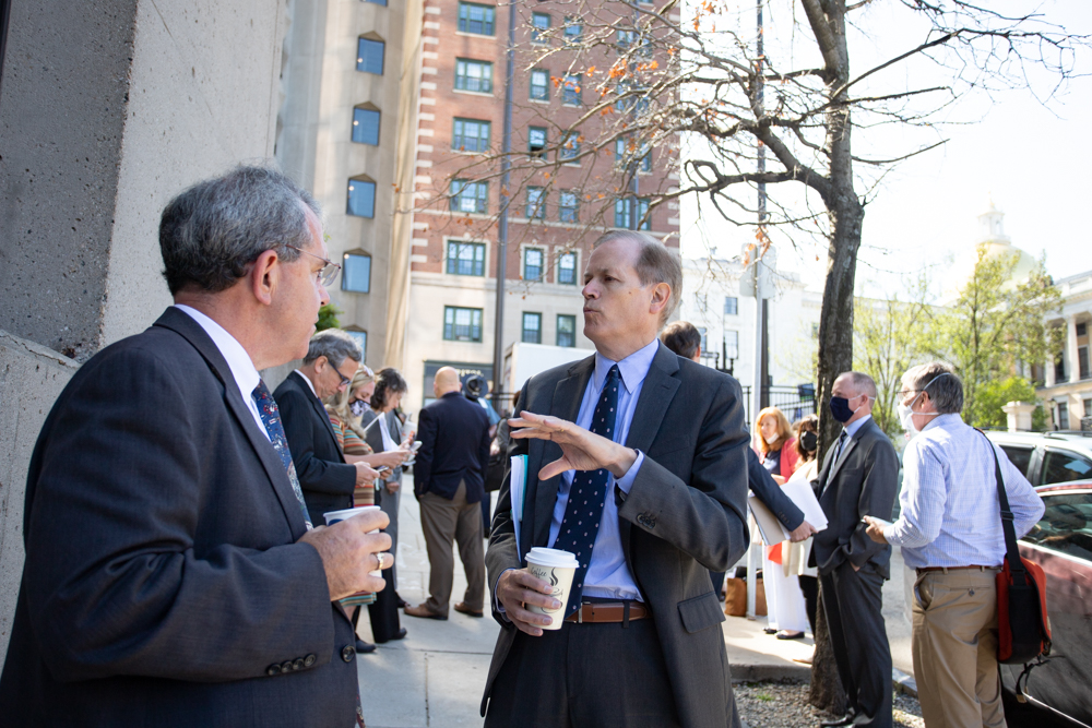Education Secretary Jim Peyser talks to a fellow evacuee on Bowdoin Street after an emergency alarm interrupted Tuesday's Board of Education meeting in the McCormack State Office Building. [Sam Doran/SHNS]