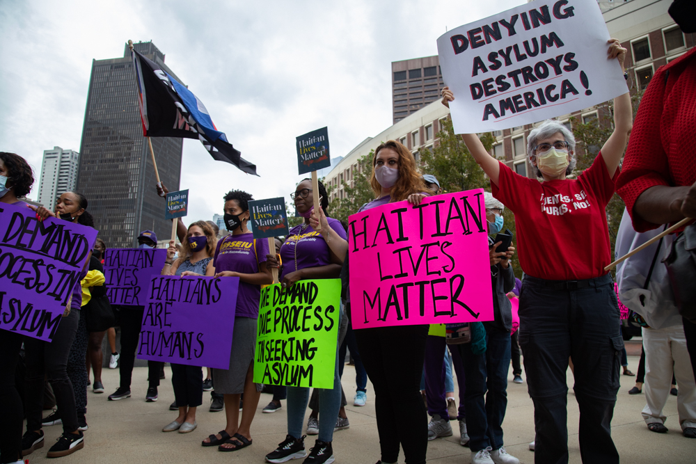 Protesters hold up signs in support of Haitian migrants at the southern border at a rally outside the JFK Federal Building in Boston Friday. A number of elected officials from Boston attended the event and criticized Biden administration immigration policies and the treatment of those trying to enter the United States. [Chris Van Buskirk/SHNS]